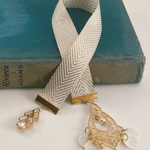 "Cotton ribbon bookmark in gold and white chevron, adorned with a gold and rhinestone charm and a large, gold-tone pendant with white shell accents Size: approx. 12"" X 1"""