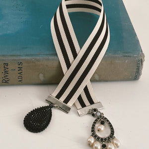 "Cotton ribbon bookmark in contrasting black and white stripes, adorned with a black rhinestone beaded pendant and a black stone-encrusted charm Size: approx. 12"" X 1"""