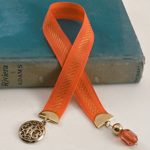 "Cotton ribbon bookmark in coral with a gold threaded stripe, adorned with a gold medallion and a gold and coral beaded charm Size: approx. 12"" X 1"""