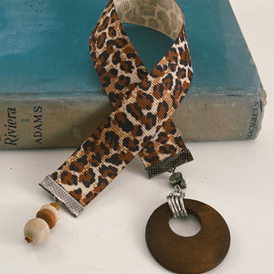 "Grosgrain ribbon bookmark in animal print, adorned with wooden beads and a large wooden/silver charm Size: approx. 12"" X 1"""