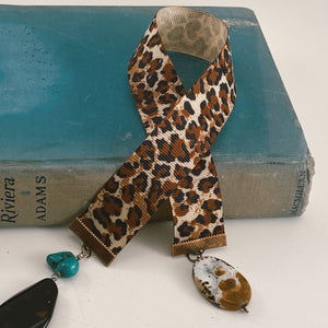 "Grosgrain ribbon bookmark in animal print, adorned with stone charms in brown, black and turquoise Size: approx. 12"" X 1"""