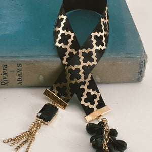 "Satin ribbon bookmark in black and gold, adorned with a black and gold tassel and a black beaded accent Size: approx. 12"" X 1"""