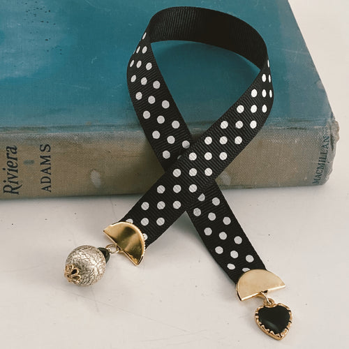 Grosgrain ribbon bookmark in black with white polka dots, adorned with a black and gold heart charm and a pearlesque beaded accent Size: approx. 12