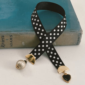 "Grosgrain ribbon bookmark in black with white polka dots, adorned with a black and gold heart charm and a pearlesque beaded accent Size: approx. 12"" X 1"""