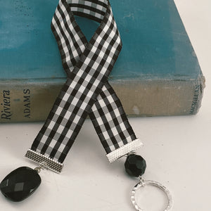 "Mesh ribbon bookmark in black and white gingham, adorned a both ends with complementary silver tone and black beaded charms Size: approx. 12"" X 1"""