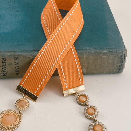 Grosgrain ribbon bookmark in coral with white stitching, adorned a both ends with complementary gold tone and pink beaded charms Size: approx. 12