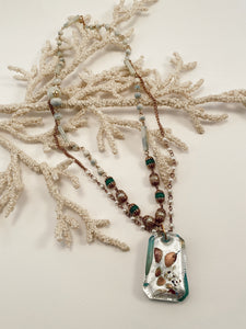 "Iridescent glass pendant strung from multiple strands of gold tone beaded chain in different hues of green and pearl. Lobster clasp closure. Size 28"" in length."