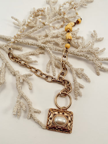 Gold and pearl pendant strung from various chains and beaded necklace pieces. Adjustable hook closure. Size 30