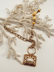 "Gold and pearl pendant strung from various chains and beaded necklace pieces. Adjustable hook closure. Size 30"" in length."
