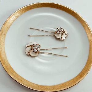 "Blush enamel and rhinestone earrings paired with sturdy gold tone hair pins. Size 2.75"" in length"