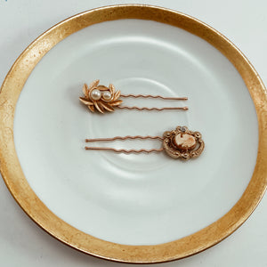 "Coordinating cameo and pearl earrings paired with sturdy rose gold tone hair pins. Size 2.5"" in length"