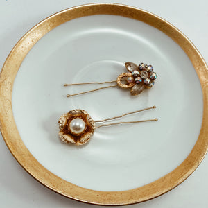"Coordinating rhinestone and pearl earrings paired with sturdy gold tone hair pins. Size 2.75"" in length"