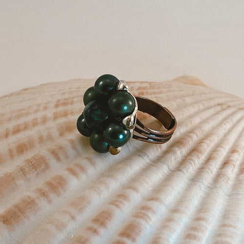 Adjustable size copper ring, adorned with a beaded vintage earring in dark green with gold accents