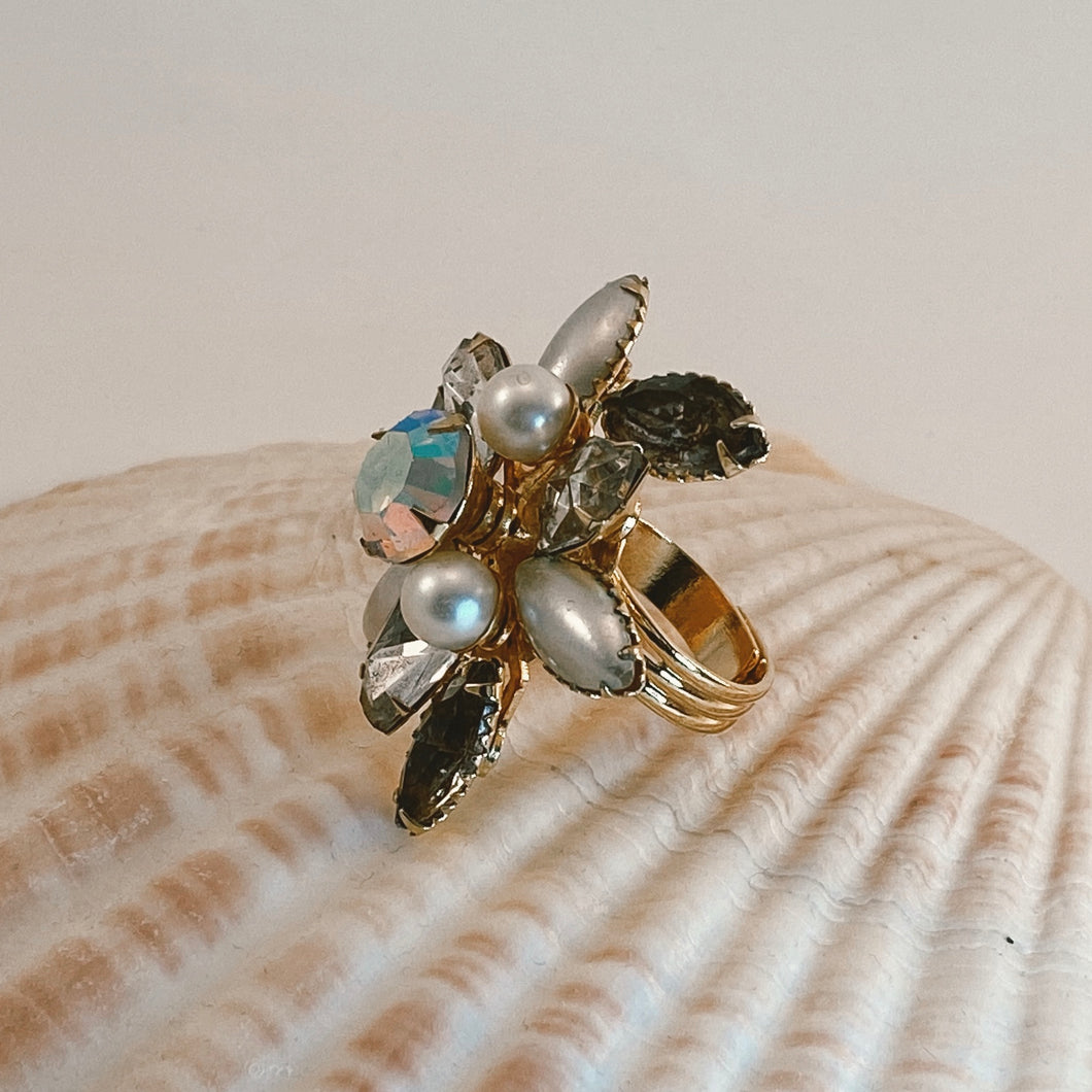 Adjustable size gold tone ring, adorned with a rhinestone vintage earring in all shades of gray, pearl and white with gold accents