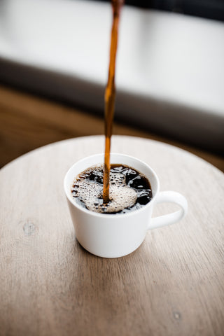 Brewed coffee pouring into a cup