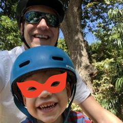 Child smiling at the camera whilst riding on dad's mountain bike on a Feva Star Seat
