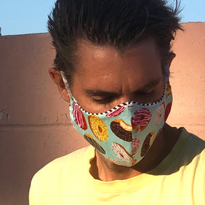 Man showing detail of Donut Go Out! reusable, reversible and washable face mask. Features integrated filter pocket. Made from three layers of 100% cotton. Designed and manufactured by Mr. Pink's based in California. Made in USA.