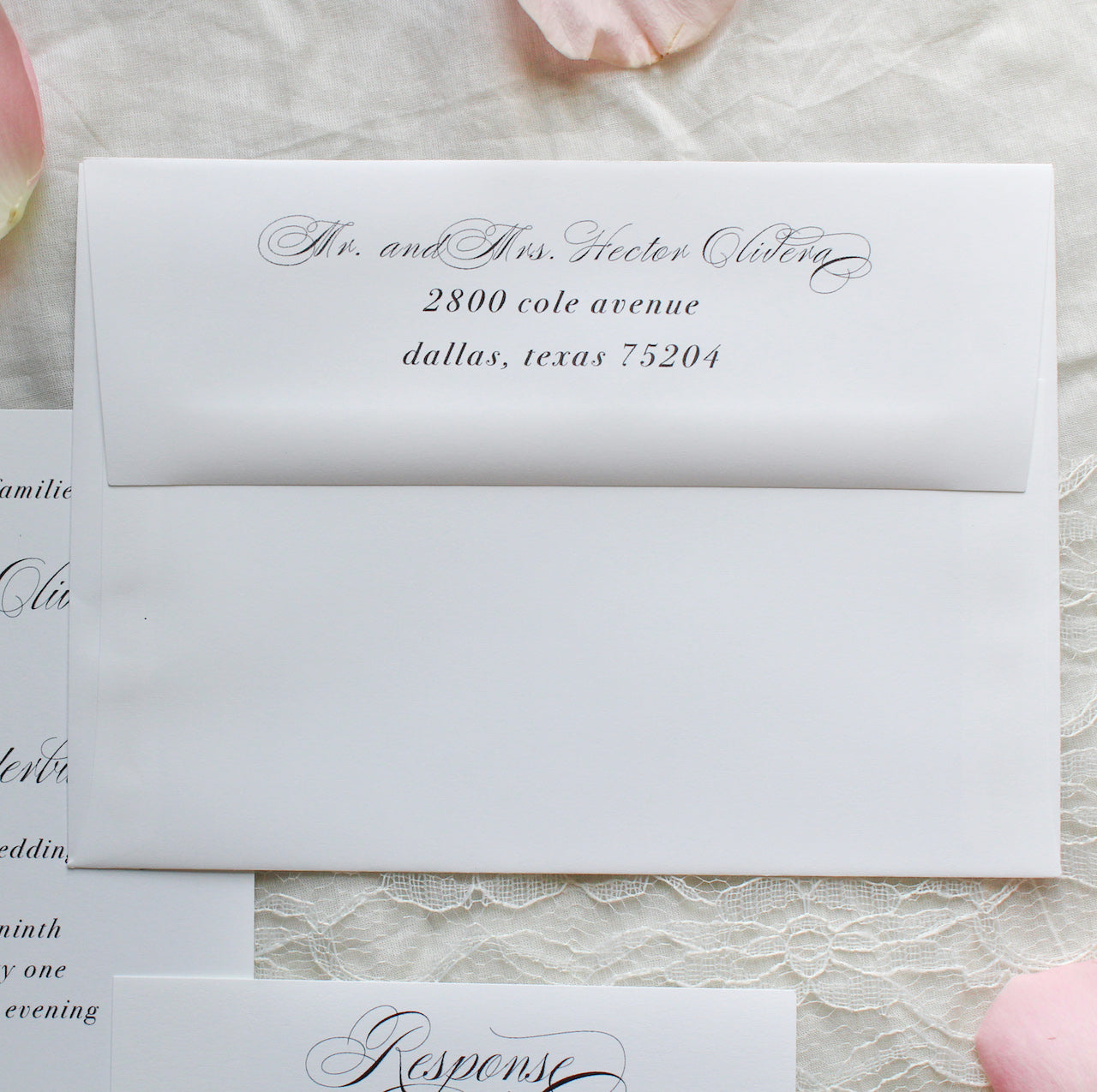 elegant wedding invitations and envelope with calligraphy script, sustainably printed on recycled paper