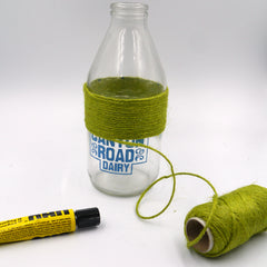 A tube of UHU glue lays on the table next to a milk bottle which has been half wrapped in green twine