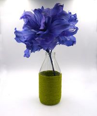 A milk bottle that has been wrapped from the shoulders down in green twine sits on a white backdrop. It has a royal blue feather flower inside it, to show it being used as a vase