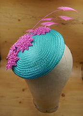 A turquoise blue circular straw hat base sits jauntily on a mannequin head. On the base, there are several hot pink beaded motifs in a starburst design, and 5 arrowhead design ostrich feather motifs, also in hot pink