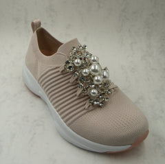 A large brooch is pinned to the front of the trainers. The brooch has large pearls and diamante jewels on it.