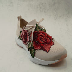 A trainer is pictured with a large embroidered rose motif sewn across the front