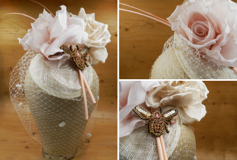 A millinery creation of a blush pink sinamay hat base, topped with large pink faux roses and pale spotted veiling. In between the roses are 2 pale pink ostrich quills and a diamante bee motif, coloured rose gold