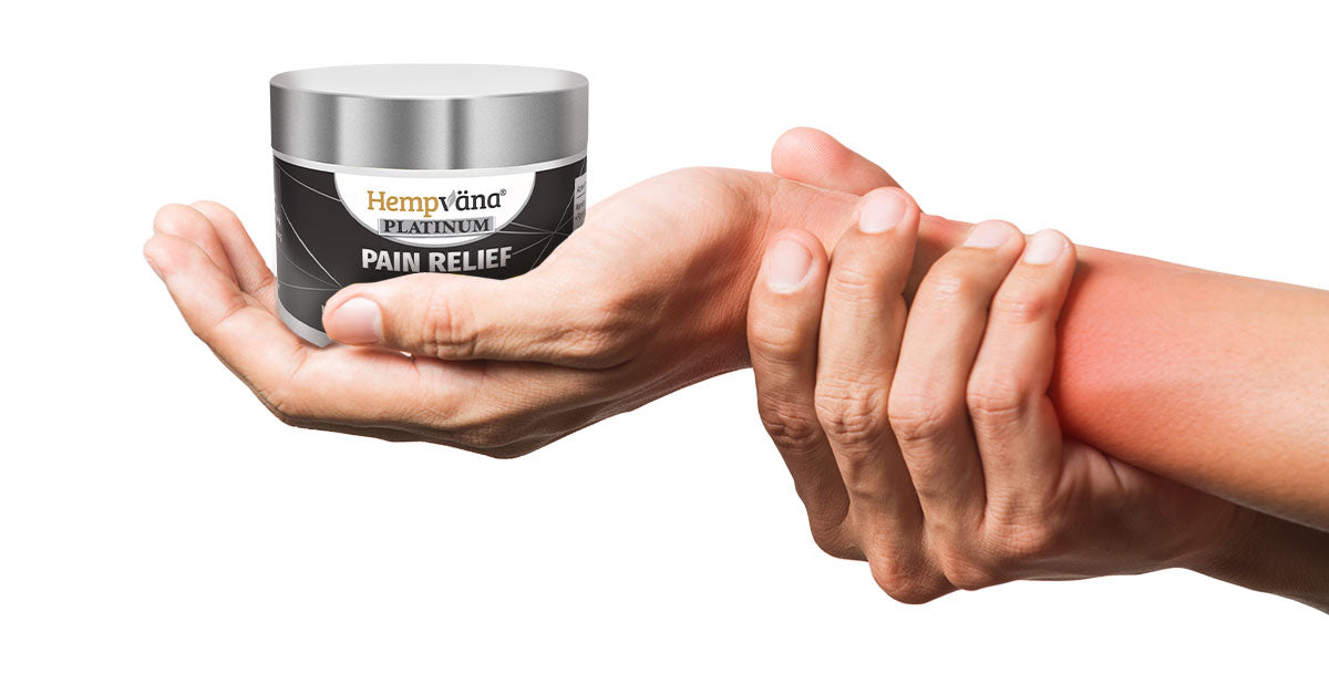 Hand holding sore wrist; open palm holding Hempvana Platinum Pain Relief Cream