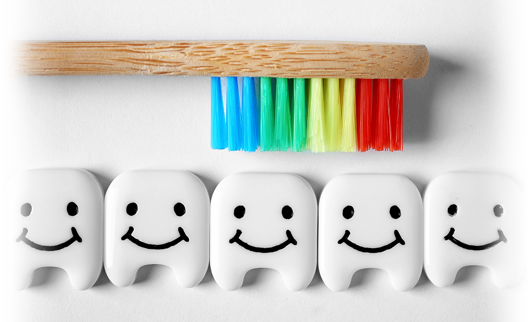 Smiling fake teeth with a bamboo toothbrush with rainbow bristles facing them