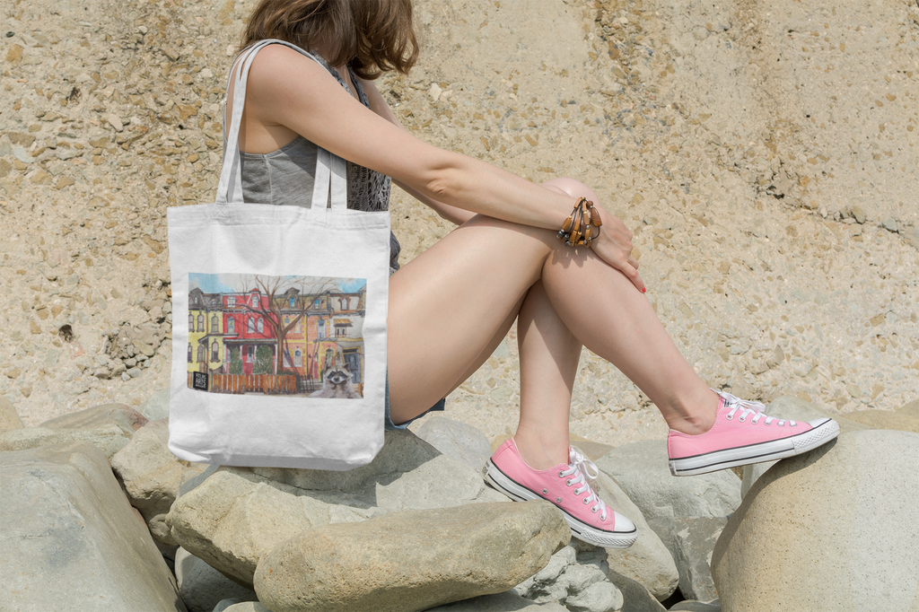 Tote bag decorated with Victorian houses of Toronto and a whimsical raccoon illustration