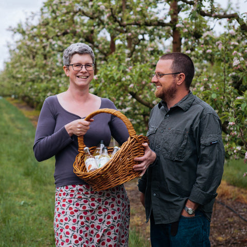 Kate and Dean holding a basket of NewLeaf Orchard sparkling juice