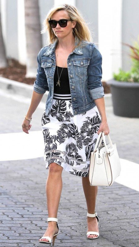 Reese Witherspoon wearing a J.O.A. Tropical Safari Skirt, a black top, and a jean jacket.