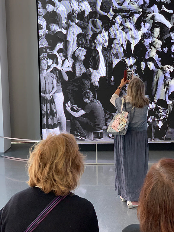 Woman taking photo of a portion of the mural titled The Chronicles of San Francisco by artist JR. The subject in the mural is artist Jay Brockman. This mural is installed in the public gallery of SFMOMA.