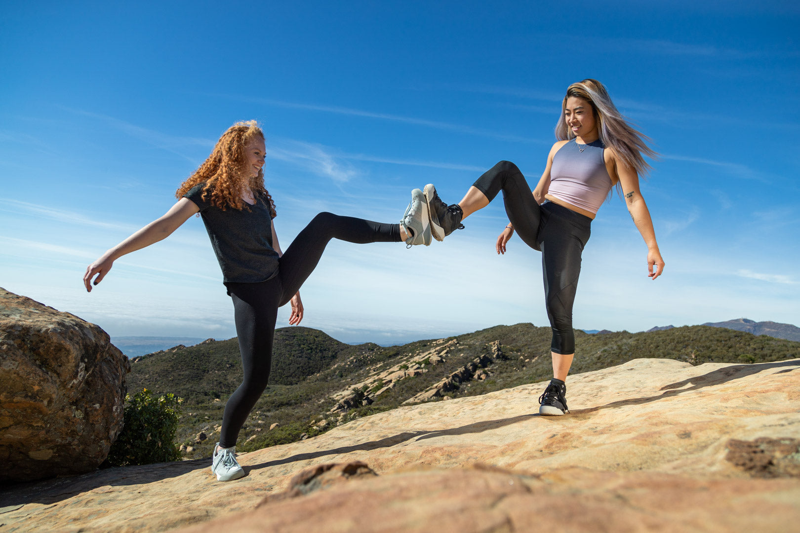 Two women tapping feet at the top of a mountain