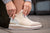 White KO-Z SNPR Mid medial side with women's hands manicured in grey pulling them on