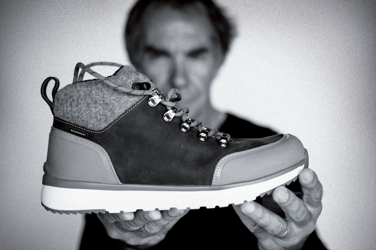 black and white image of a sneaker  boot held by innovator and business man, Jean-Luc Diard