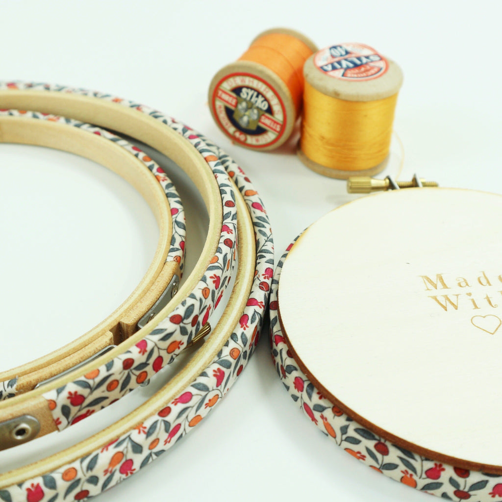 embroidery hoops covered with orange and red berry fabric