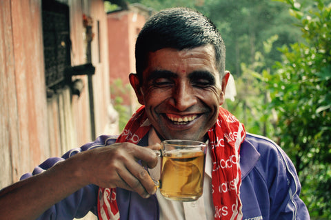 Nepali man with large grin as he moves his tea cup closer to take a sip