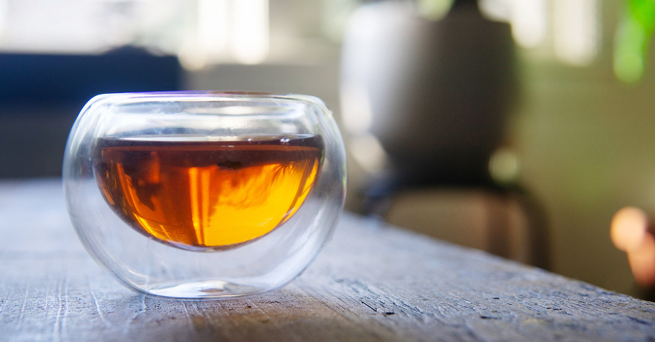Glass teacup full of tea on a wooden table