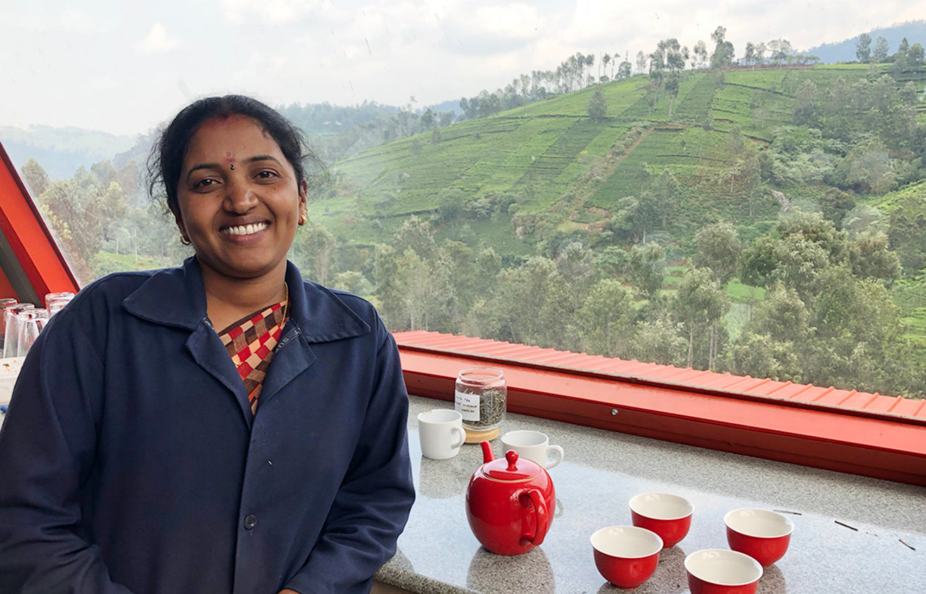 Female tea factory worker in her navy uniform leaning against a tea table, looking out into the lush tea fields, with a red tea set next to her.
