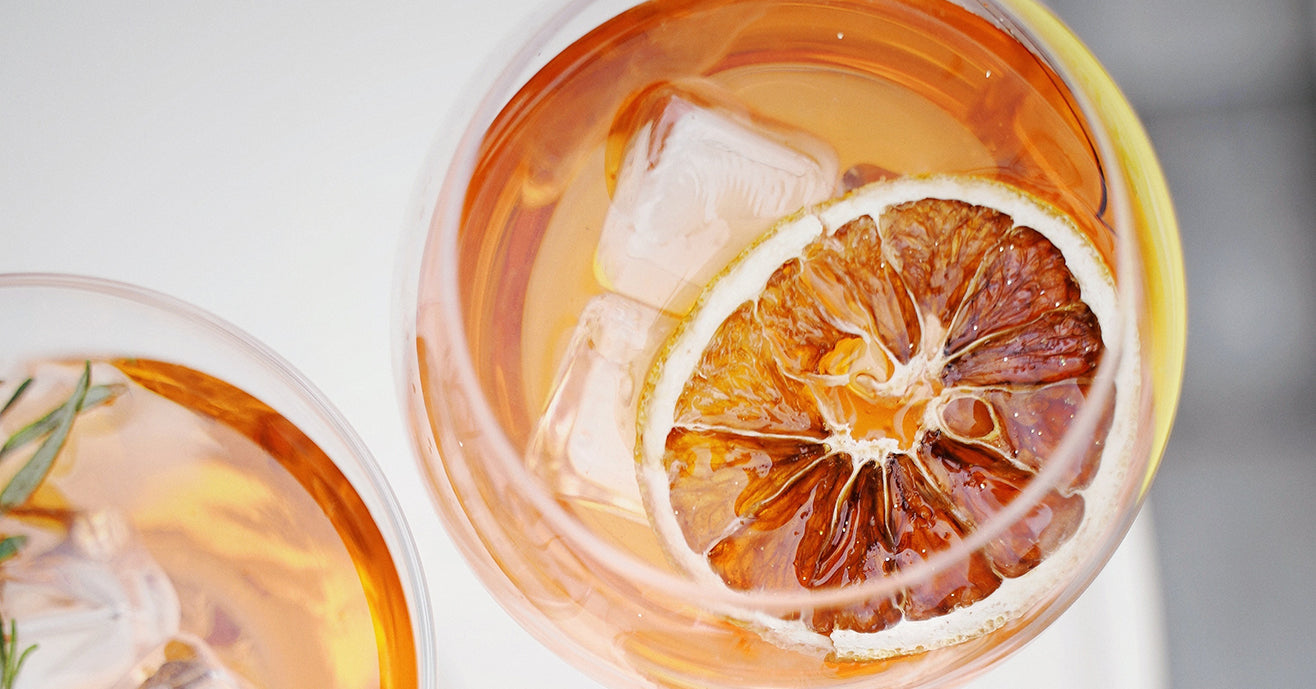 Iced tea with a wedge of orange in glasses