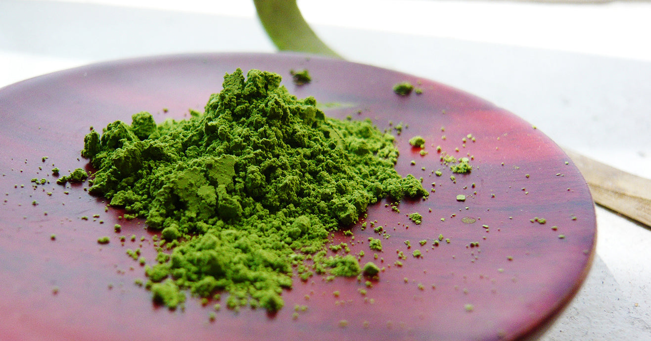 Powdered green tea, matcha, on small wooden plate