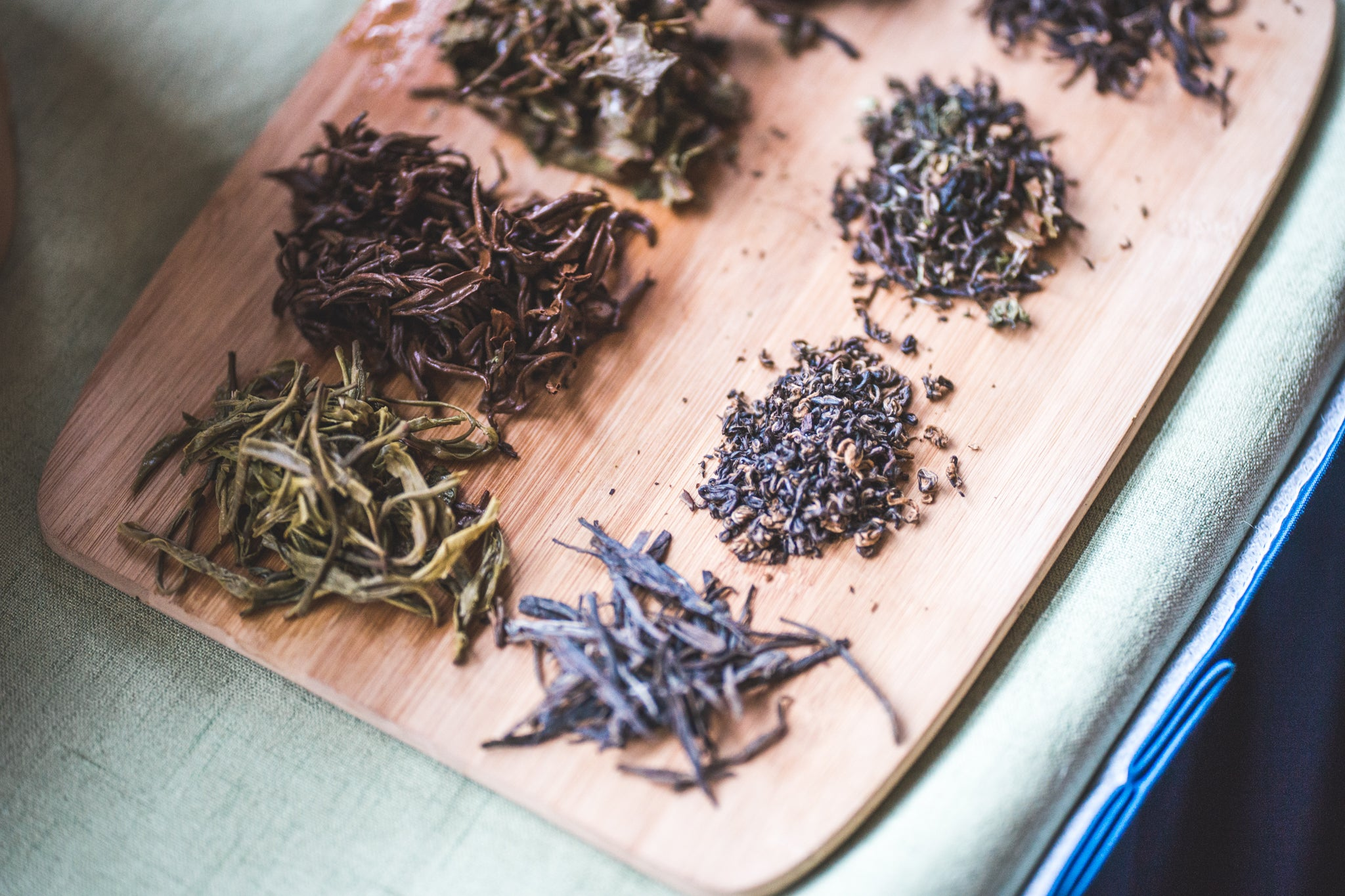 Loose leaf Indian and Nepali tea laid out on a cutting board. Wet and dry leaf.