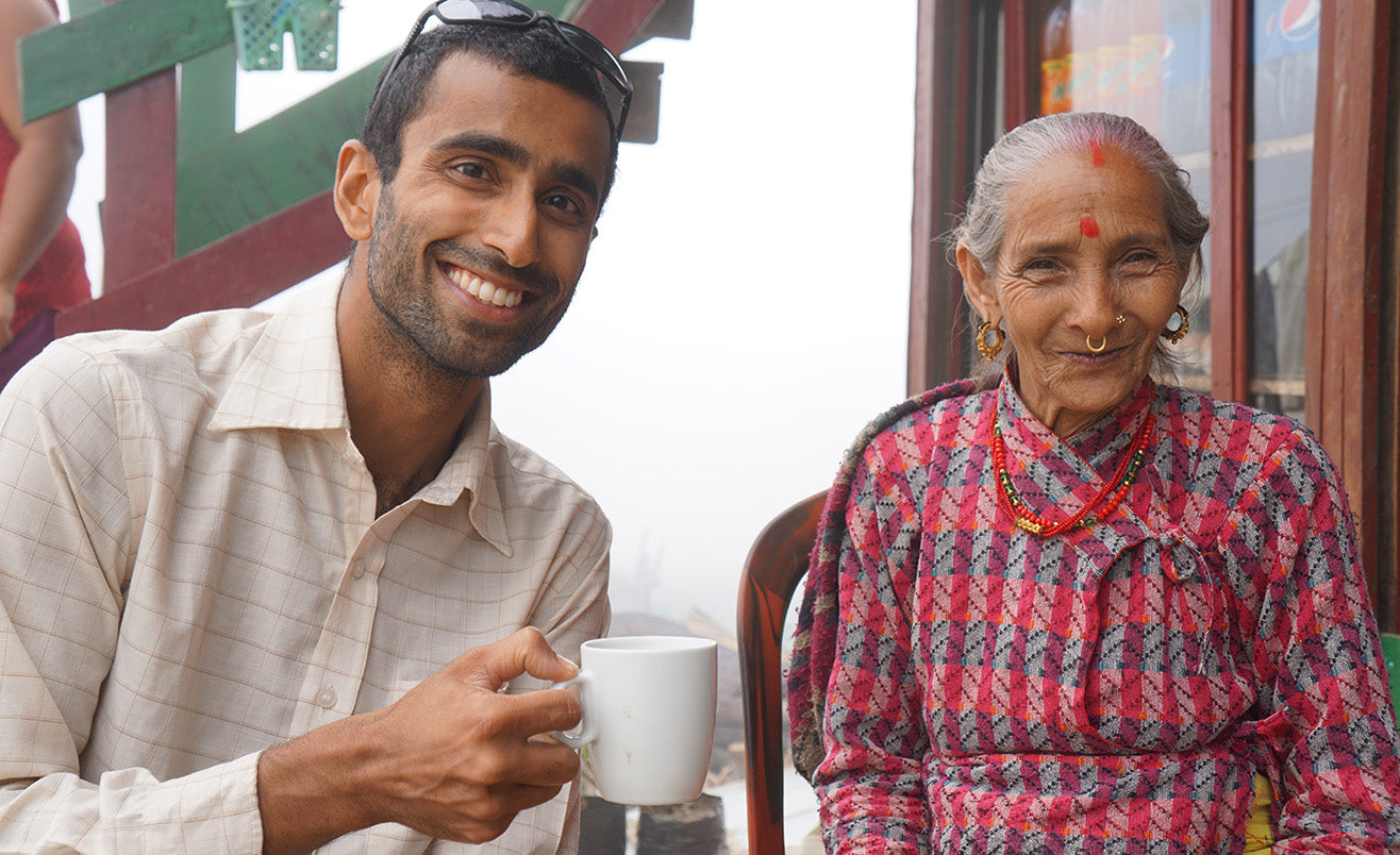 Raj drinking tea with an elderly woman in Nepal