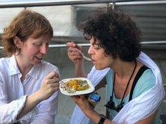 Two American woman tasting Indian street snacks