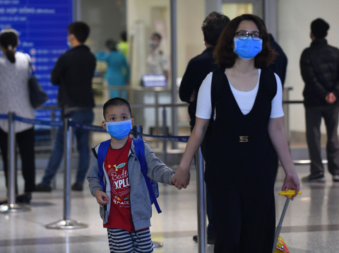 This picture taken on February 2, 2020 shows travellers wearing protective facemasks at Noi Bai international airport in Hanoi. Picture: AFP