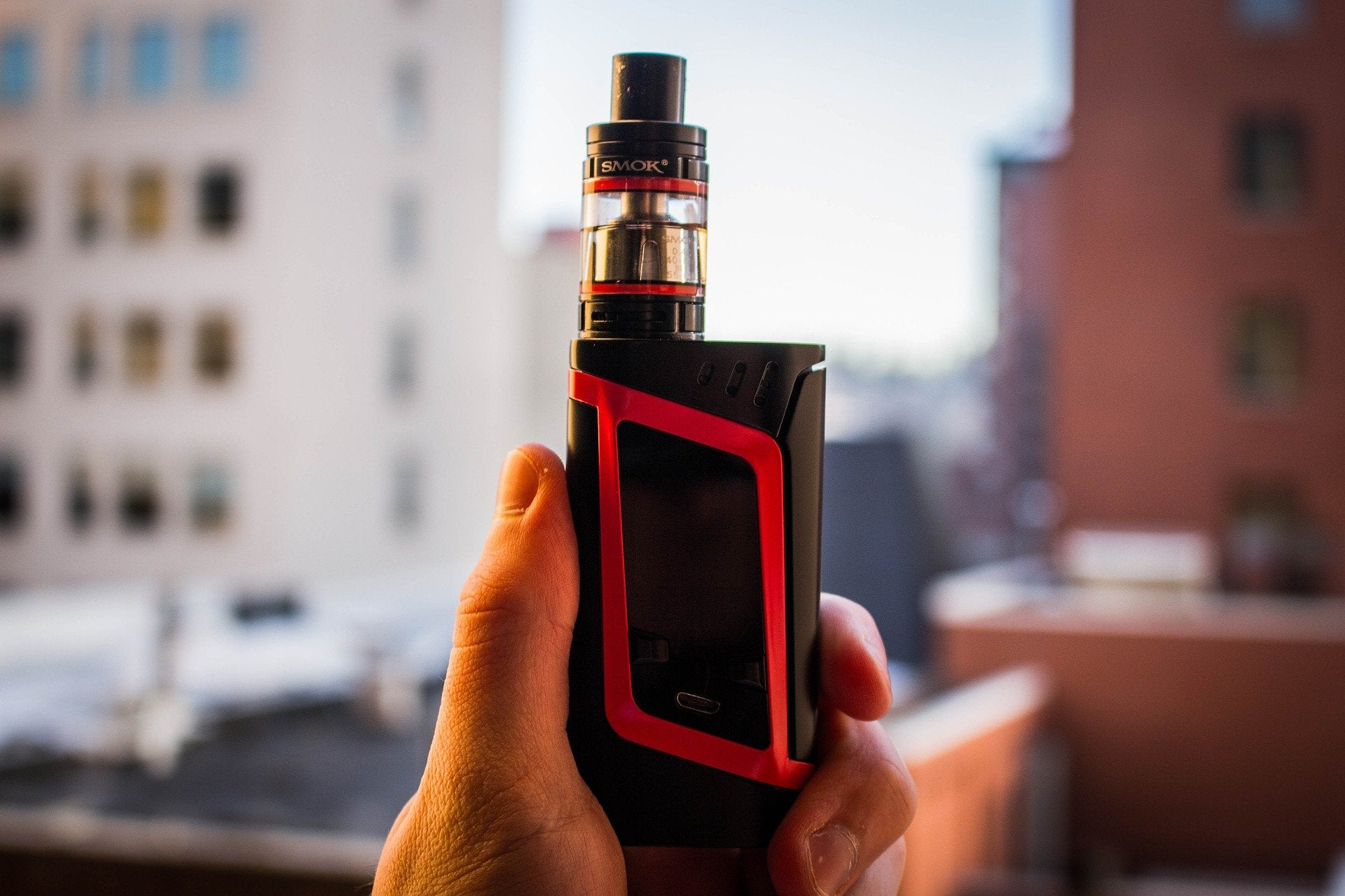 black and red vape mod in a person's hand