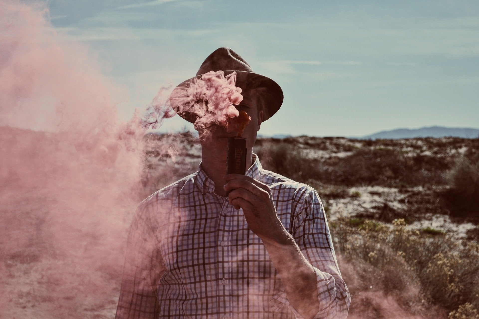 person vaping in a bushing with pink smoke