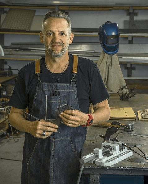 Photo of Phil Walters, founder and owner of Metalbird, holding a Metalbird in his workshop